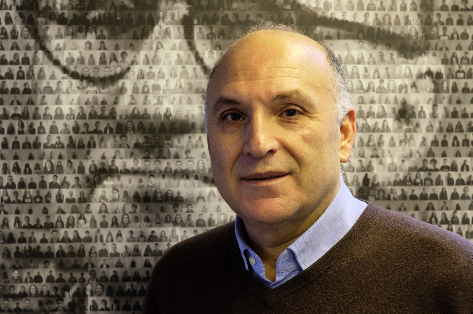 Porträt: Mann mittleren Alters mit wenigen, sehr kurzen Haaren. Aus einem dunkelbraunen Pullover schaut der Kragen eines hellblauen Hemdes hervor