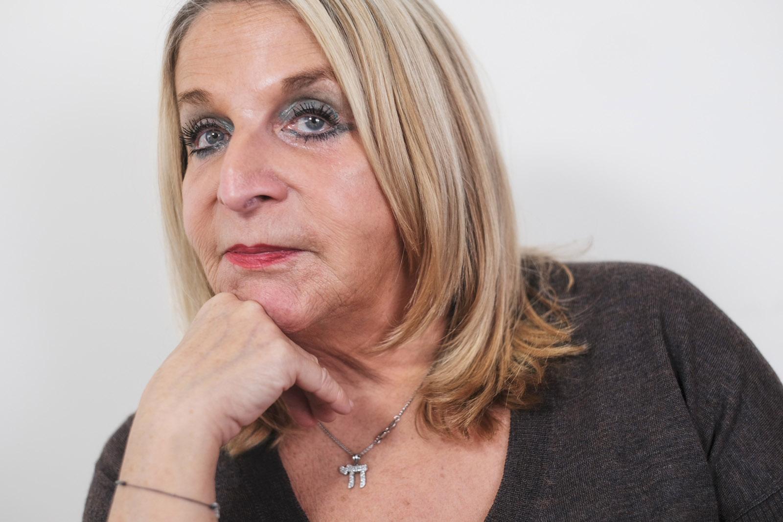 Blonde Frau mittleren Alter mit ausgeschnittenem schwarzen Pullover